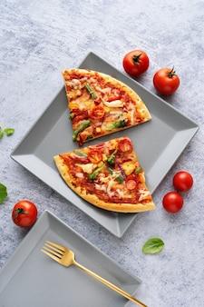 Deux morceaux de pizza végétarienne sur fond bleu clair