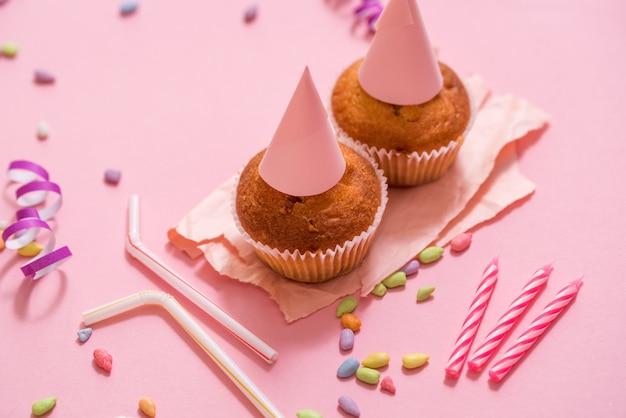 Deux muffins au chocolat, une bougie d'anniversaire. fête pour les filles. caps et tinsel et bonbons multicolores