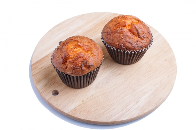 Deux muffins aux carottes sur planche de cuisine en bois isolé sur blanc