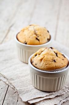 Deux muffins frais faits maison sur des bols blancs en céramique sur une serviette en lin.