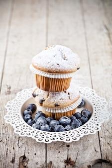 Deux muffins frais faits maison avec du sucre en poudre et des bleuets sur une plaque blanche sur une table en bois rustique.