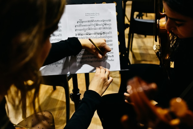Deux musiciennes corrigeant une partition avec un crayon avant que l'orchestre ne commence à jouer.