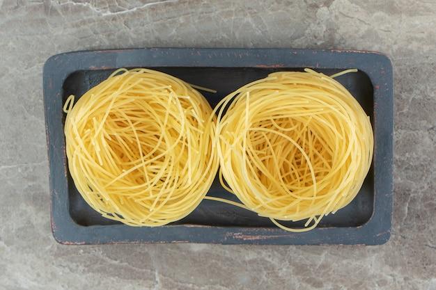 Deux nids de nouilles non cuites sur plaque noire
