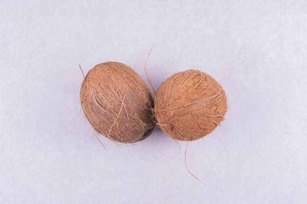 Deux noix de coco isolés sur une surface blanche.