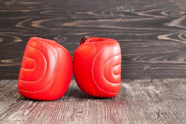 Deux nouveaux gants de boxe rouges sur fond de bois noir