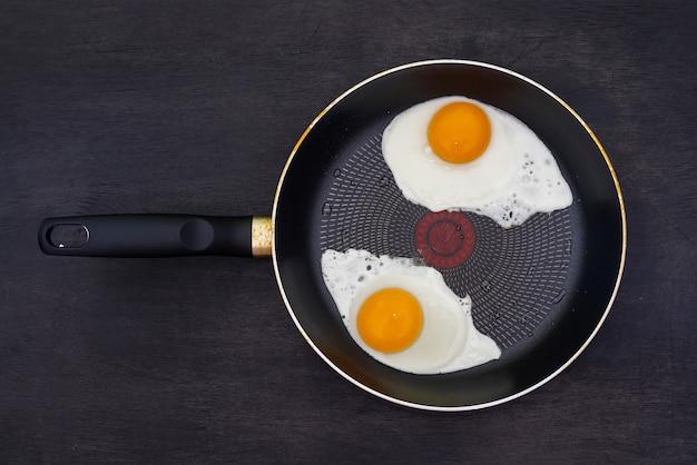 Deux œufs au plat dans une poêle sur un bois sombre. vue de dessus.