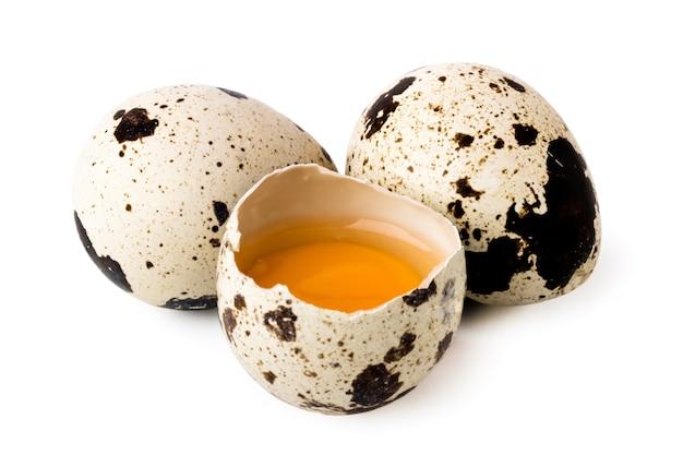 Deux œufs de caille et cassés sur blanc