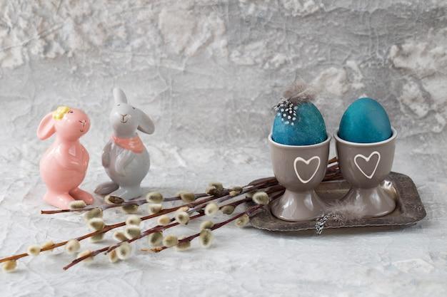 Deux oeufs peints sur un support sur un vieux plateau d'argent, des plumes, un saule et deux lapins à proximité