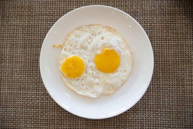 Deux œufs sur le plat dans un plat servant un petit-déjeuner sain