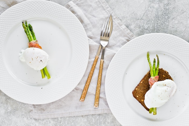 Deux œufs pochés sur des asperges grillées et enveloppées dans du bacon.