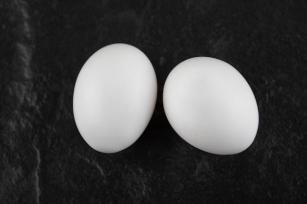 Deux œufs de poule blancs frais sur un tableau noir.