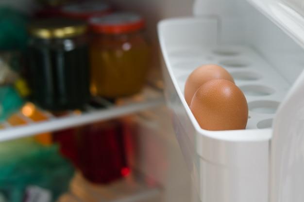 Deux œufs de poule sur une étagère de la porte de réfrigérateur