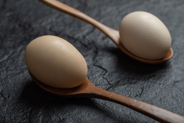 Deux œufs de poule frais sur des cuillères en bois.