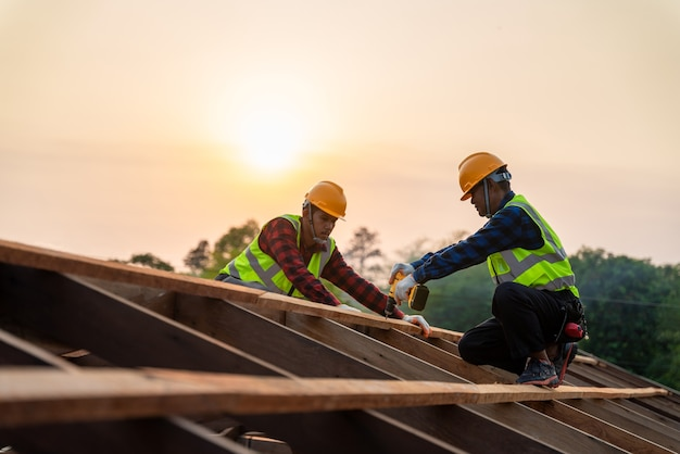 Deux ouvriers de construction asiatiques installent un nouveau toit, des outils de toiture, une perceuse électrique utilisée sur de nouveaux toits de structure de toit en bois, un concept de construction de travail d'équipe.