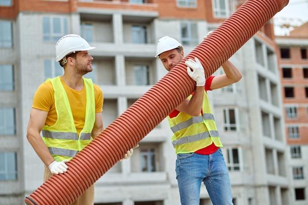 Deux ouvriers qualifiés portant des gilets de sécurité et des casques de protection érigeant un lourd tuyau de drainage ondulé avec des mains gantées