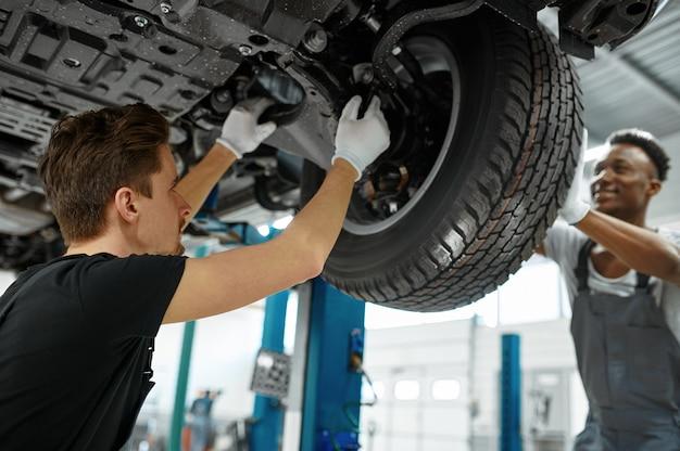 Deux ouvriers réparent la roue dans un atelier mécanique.