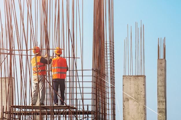 Deux ouvriers en salopette et casques de protection sur chantier en plein air