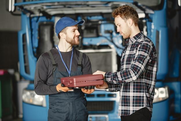 Deux ouvriers en uniforme. travailleurs avec des outils. jour ouvrable.