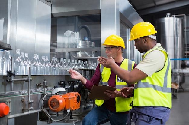 Deux ouvriers d'usine discutent tout en surveillant la chaîne de production de boissons