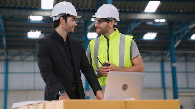 Deux ouvriers d'usine travaillant et discutant du plan de fabrication dans l'usine. concept d'industrie et d'ingénierie.