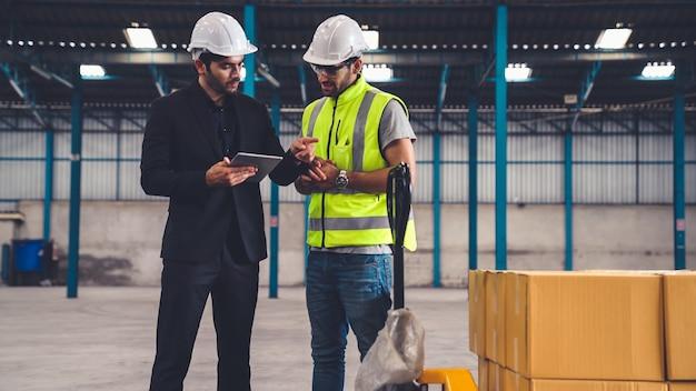 Deux ouvriers d'usine travaillant et discutant du plan de fabrication dans l'usine.