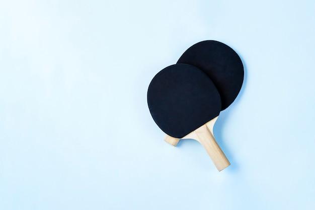 Deux pagaies de ping-pong noires sur fond bleu clair