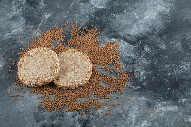 Deux pain croustillant et sarrasin non cuit sur une surface en marbre