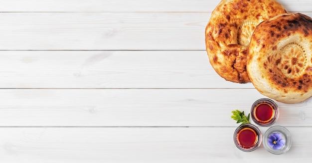 Deux pain tandoor fraîchement cuit sur une surface en bois blanc à côté de verres d'armudu avec du thé. mise à plat, copiez l'espace pour le texte ou la recette. pain traditionnel en asie centrale et au moyen-orient.