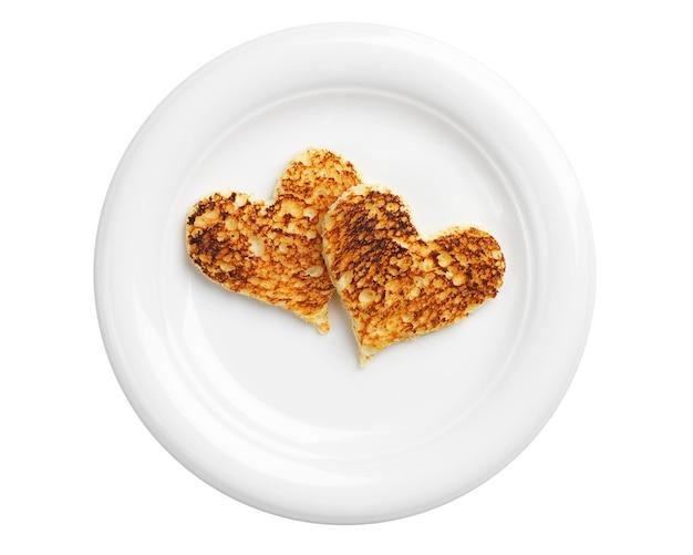 Deux pains grillés en forme de coeurs dans une assiette isolée sur fond blanc