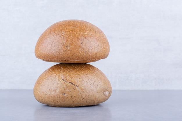 Deux pains à hamburger empilés sur une surface en marbre