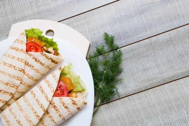 Deux pains pita avec garniture, escalopes de poulet aux légumes enveloppés dans du pain pita