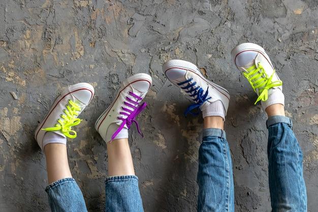 Deux paires de jambes d'une fille et d'un jeune homme portant un jean bleu et des baskets blanches