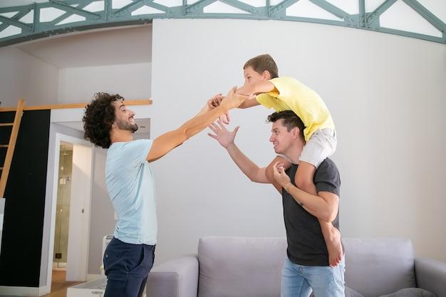 Deux papas et fils joyeux s'amusant à la maison, garçon à cheval sur le cou de l'homme. vue de côté. concept de famille et de parentalité