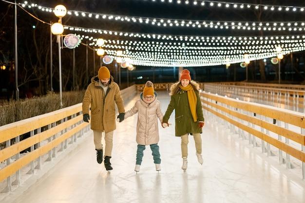 Deux parents apprennent à leur fille à patiner, ils se tiennent la main et patinent sur une patinoire à l'extérieur
