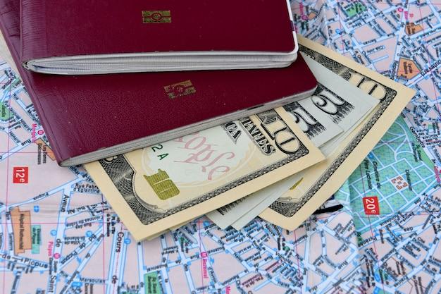 Deux passeports et des billets de quelques dollars sur un fond de carte de la ville