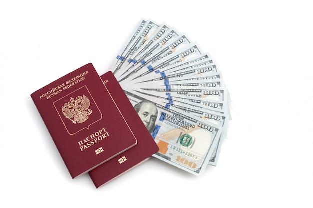 Deux passeports rouges et billets de cent dollars sur fond blanc.