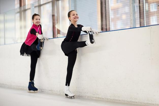 Deux patineurs artistiques s'étirant les jambes