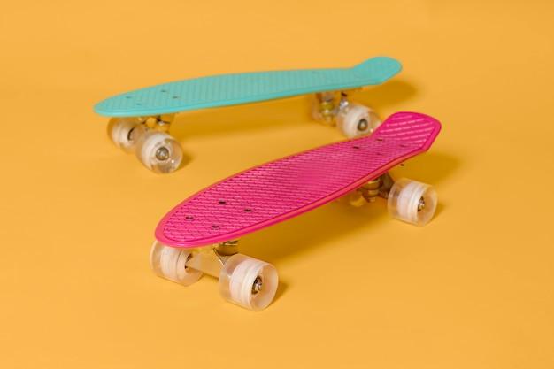 Deux penny skateboard rose et vert isolé sur fond jaune