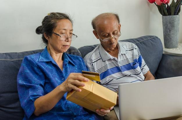 Deux personnes âgées asiatiques faisant du shopping en ligne. senior holding carte de crédit assis sur un canapé avec un ordinateur portable à la maison.