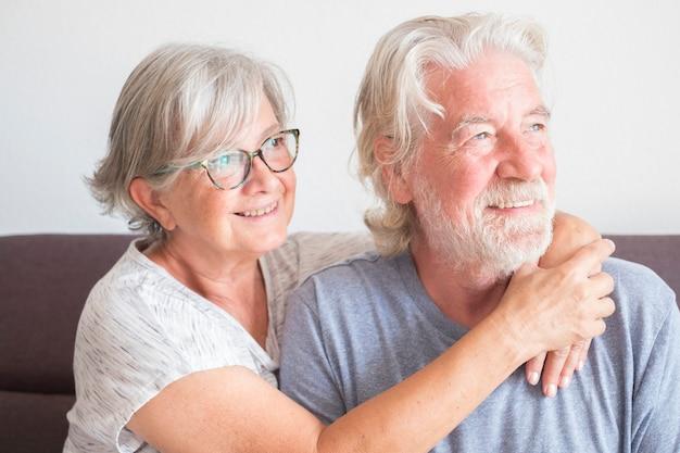 Deux personnes âgées et un couple mature de personnes assises sur le canapé à la maison se sont embrassées en regardant la caméra heureuses d'amour et d'affection