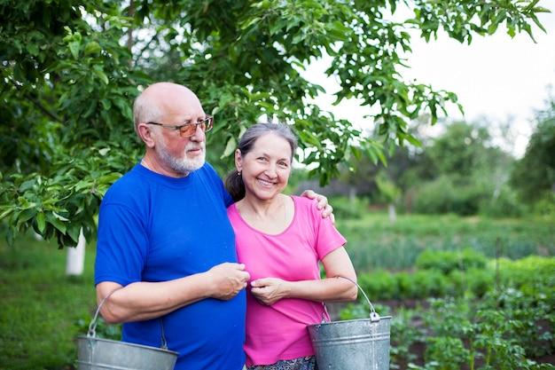 Deux personnes âgées dans un potager avec des seaux