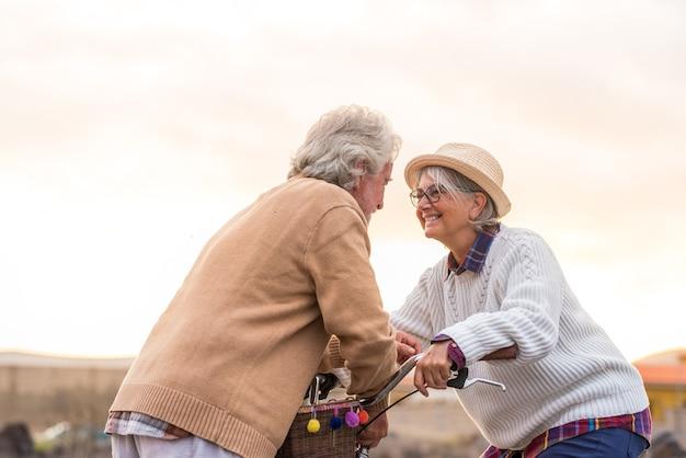 Deux personnes âgées ensemble souriant et s'amusant à se regarder femme mature avec un vélo