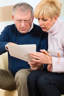 Deux personnes âgées ont reçu une lettre, peut-être un rappel ou un projet de loi, mais il s'agit probablement de l'avis de cotisation fiscale