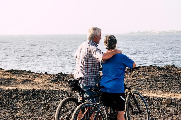 Deux personnes âgées sur une plage rocheuse avec leurs vélos - couple de retraités étreints en regardant la mer ou l'océan - mode de vie sain et fitness