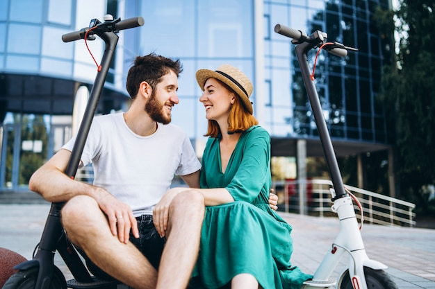 Deux personnes attrayantes se détendent près du bâtiment en verre avec leurs scooters électriques. homme et femme profitent des vacances
