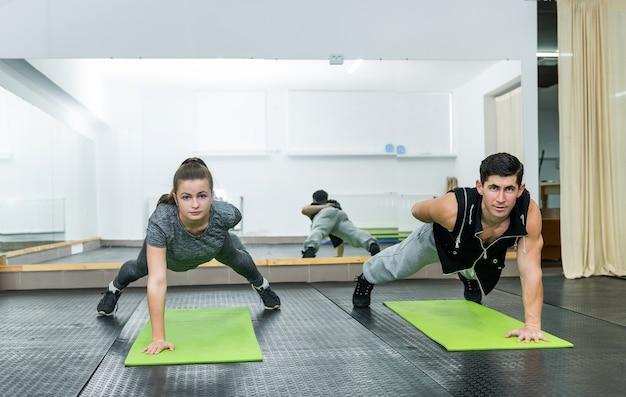 Deux personnes dans une salle de sport faisant des exercices de planche ensemble