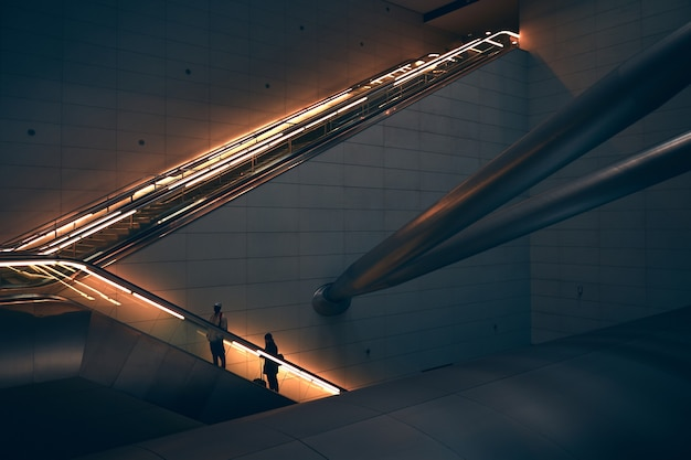 Deux personnes debout sur l'escalator