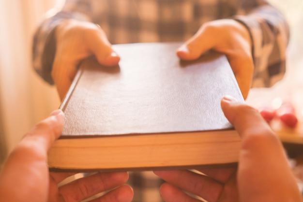 Deux personnes échangent le livre, transmettant le savoir aux jeunes générations