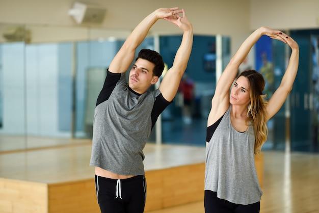 Deux personnes étendent leurs bras en gymnase.