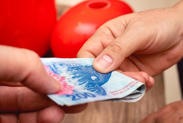Deux personnes faisant des affaires avec des factures d'argent de l'argentine en photo en gros plan